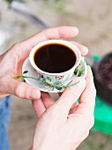 Hands holding a cup of coffee served with the Ethiopian herb tena adam