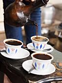 Frau serviert Kaffee aus Jabena während der traditionellen Kaffeezeremonie in Äthiopien