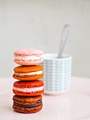 A pile of macarons in front of a cup of coffee