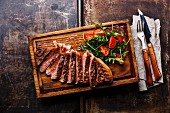 Sliced grilled beef barbecue Striploin steak and salad with cherry tomatoes and arugula