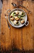 Escargots de Bourgogne (Weinbergschnecken mit Kräuterbutter) in Aluminiumpfanne auf rustikalem Holzuntergrund