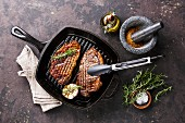 Grilled Black Angus Steak Striploin on frying cast iron Grill pan on dark background