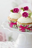 Mit rosa Zuckerrose verzierte Cupcakes auf einem Kuchenständer