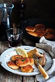 Panierte Fischpuffer mit Brotscheibe und Zitrone