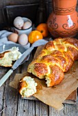 A homemade Hefezopf (sweet bread plait from southern Germany) with orange zest with a chunk broken off for Easter
