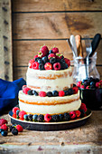 A two-tier semi-naked cake with vanilla cream and fresh berries