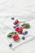 Kandierte Rosenblüten, Veilchenblüten und Pfefferminzblätter auf altem Tuch