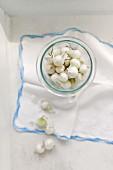 Kleine rohe Perlzwiebeln im Weckglas und daneben auf einem alten Tuch