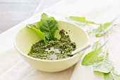 Home-made dandelion pesto in a bowl with fresh dandelion leaves