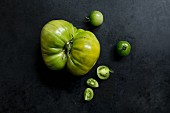 Two varieties of green tomatoes on a dark metal surface (varieties: Green Doctor and Absinthe)