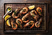 Roasted tiger prawns with green sauce and lemon on metal baking sheet background
