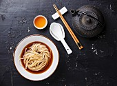 Asian Ramen noodles with broth in bowl and Tea on dark background