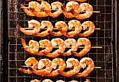 Grilled fried Prawns on skewers on metal grid baking sheet background
