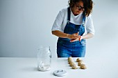 Girl forming dough for bagels on a white table