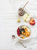 Bircher muesli with fresh friut, berries and honey over white painted wooden background