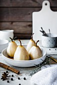 Spiced poached pears in a white bowl next to cinnamon and star anise