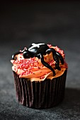 A Halloween cupcake with orange buttercream and a spider