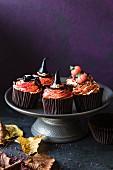 Halloween-Cupcakes mit orangefarbener Buttercreme und verschiedenen Fondant-Dekos auf einem Kuchenständer