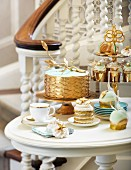 A cake and desserts in white and gold for a wedding