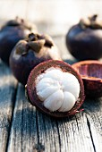Mangosteen, whole and cut open, on a wooden table