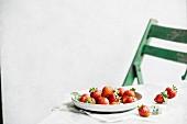 Tischszene mit Erdbeeren und grünem Stuhl