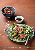 Beef steak with rocket, dried tomatoes and passionfruit & balsamic vinegar dressing