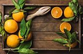 Frische Orangen mit Blättern und Zitruspresse aus Holz auf Holztablett