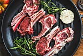 Raw uncooked lamb meat chops with rosemary and garlic in black iron grilling pan