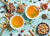 Two cups of healthy herbal tea with mint, cinnamon, dried rose and camomile flowers in spoons
