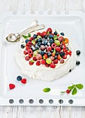Homemade Pavlova cake with fresh garden berries served with silver spoons on white baking tray
