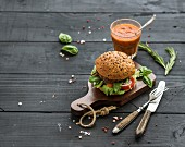 Fresh homemade burger with vegetables and tomato sauce on wooden serving board over dark wooden background