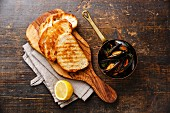 Mussels in copper pot, bread toasts and lemon on wooden background