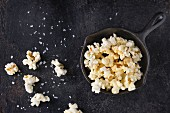 Prepared salted popcorn served with sea salt in small iron-cast pan over black iron textured background