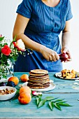 Pancakes on the wooden table and girl in denim dress behinde