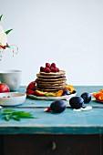 Gestapelte Pancakes mit Früchten garniert auf türkis Holztisch