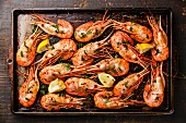 Roasted shrimp comb with greens, spices and lemon on metal baking sheet background