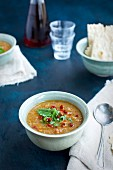 Red Lentil Soup topped with sun dried tomato and arugula in ceramic bowls