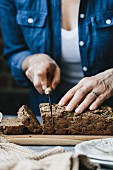 A woman is slicing a loaf of vegan zucchini and walnut bread