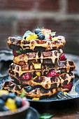 Several brioche waffles are stacked and layered with fresh fruits and drizzled with maple syrup