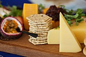 Chunks of cheese with biscuits on a wooden board garnished with watercress