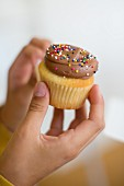 Hands holding a cupcake topped with chocolate cream and colourfu hundreds and thousands