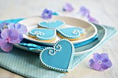 Heart-shaped biscuits decorated with blue and white icing served on a plate with flowers