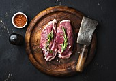 Duck breast with rosemary, spices and a butcher's cleaver on a wooden board
