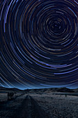 Star trails over lonely road