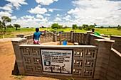 Woman using a water pump,Malawi