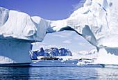 Ship through arch of iceberg off Antarctica