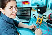 Woman soldering a printed circuit board