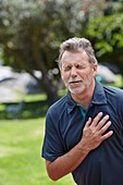 Senior man holding his chest in pain