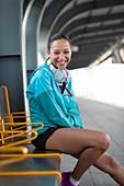 Woman sitting on railway platform smiling