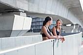 Women leaning on wall in sports wear